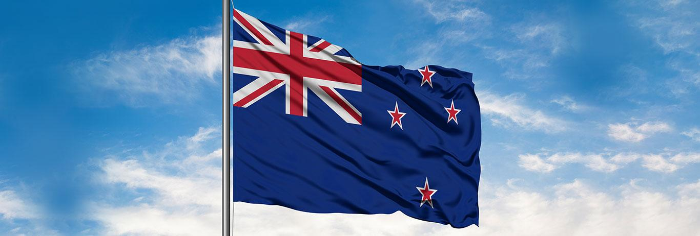 Flag of New Zealand waving in the wind against white cloudy blue sky