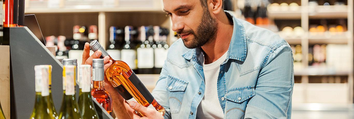 Man holding bottle of wine and looking at the label in a wine store