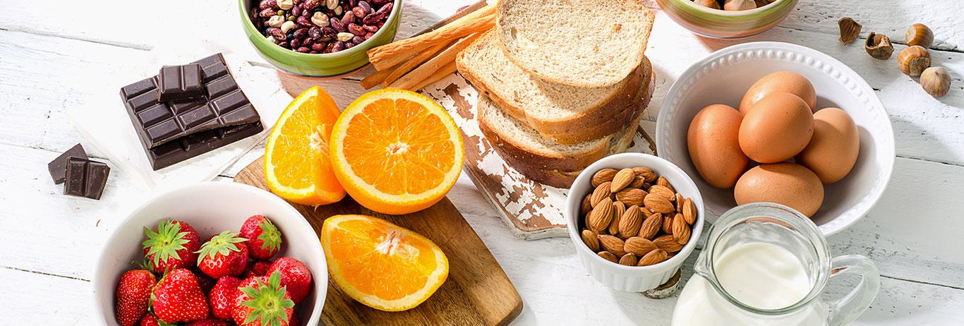 Potential allergy foods (nuts, eggs, strawberries, citrus, chocolate, milk and bread) on white background