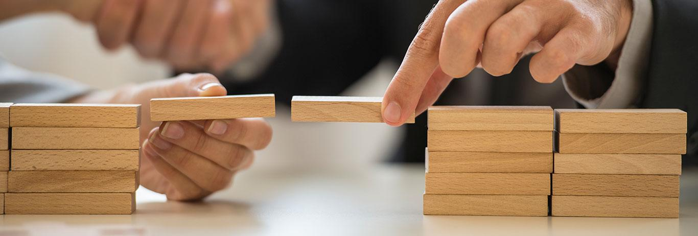 Businessman and woman holding wooden building blocks to form a bridge over a gap while clasping hands in the background